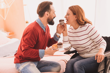 Pleasant mid aged couple resting at home while eating cup cakes Stock Photo