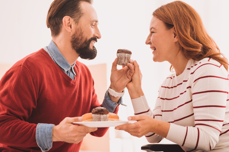Joyful pleasant couple eating cupcakes while expressing happiness at home Imagens