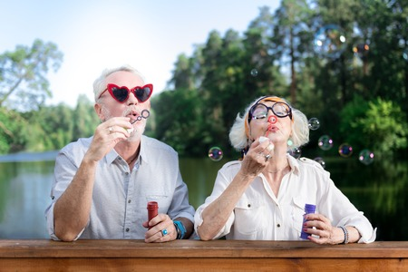 Soap bubbles. Cute retired couple wearing bright sunglasses using soap bubbles while standing on the wooden bridge