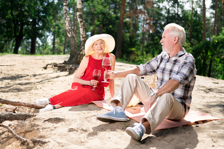 Red wine. Stylish beaming pensioners feeling relieved while drinking glasses of tasty red wine having picnic together
