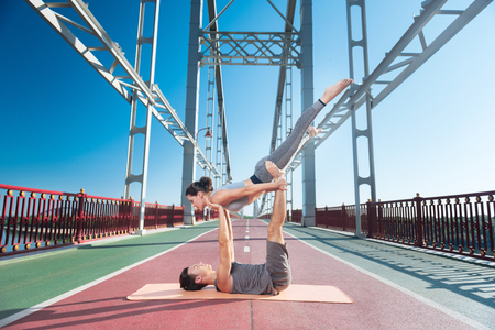 Sportive energetic man rising woman while they trying yoga 写真素材