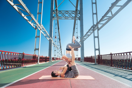 Confident progressive man supporting woman while they trying yoga