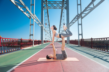 Challenging yoga. Successful appealing man assisting woman while they trying yoga