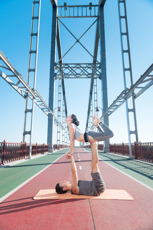 Duo driven pose. Pleasant positive man aiding woman while they trying yoga