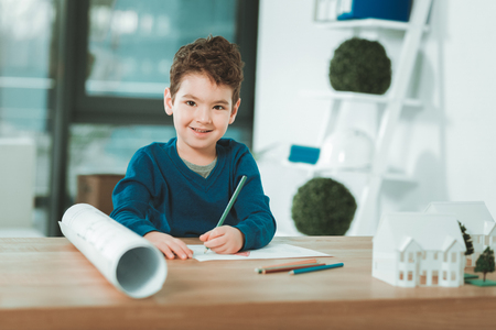 Young talent. Positive talented boy holding pencils while doing a drawing Stock Photo