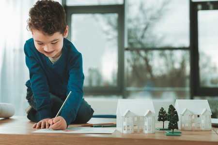 Beautiful picture. Joyful happy boy sitting on the table while drawing a picture