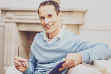 Positive mood. Cheerful nice man looking at you while holding his glasses