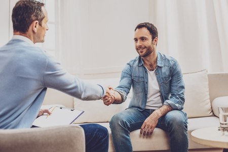 Positive delighted man looking at his psychologist while greeting him