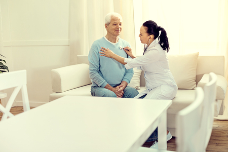 Preventive visit. Cheerful elderly man sitting on a sofa while a female doctor listening to his heart beating and lungs.