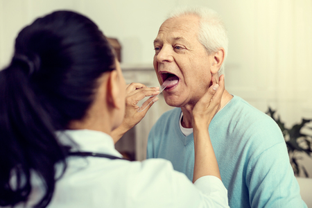 Seasonal illness. Selective focus on an elderly gentleman sitting with his mouth wide opened while attending a medical professional and checking his throat.