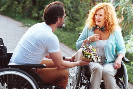 Completely amazed. Selective focus on a disabled lady beaming while getting surprised by her soulmate holding a beautiful bouquet.