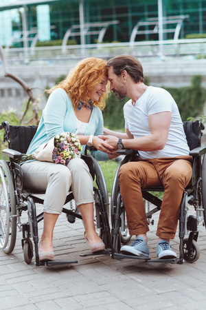 Harmonious relations. Loving mature couple sitting in their wheelchairs and smiling cheerfully while enjoying their romantic walk outdoors. 스톡 콘텐츠