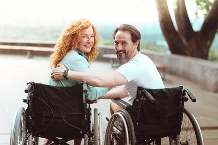 Support is what really matters. Harmonious mature couple turning their head and beaming into the camera while sitting in their wheelchairs outdoors.