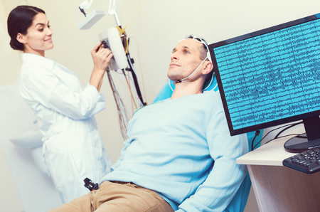 Innovative approach. Selective focus on a PC displaying brain waves on a male patient lying on an examination couch and undergoing electroencephalography procedure. Фото со стока