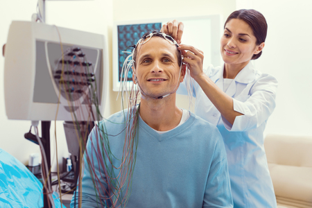 Waist up shot of a mature gentleman smiling while waiting for the nodes to be adjusted before undergoing an electroencephalography procedure. Stock Photo