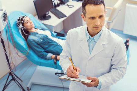 Hacer un diagnóstico. Vista superior de un trabajador médico maduro pensativo sosteniendo un portapapeles mientras escribe algo durante un análisis de electroencefalografía. Foto de archivo