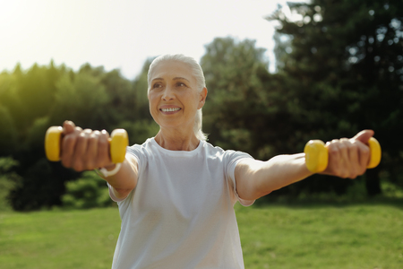 Staying active. Waist up shot of a radiant senior woman grinning broadly while exercising with weights during her workout outdoors.