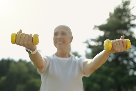 Healthy and strong. Selective focus on dumbbells held by a happy elderly lady smiling cheerfully while exercising in a local park.