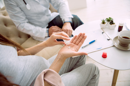 Mothers health. Close up of medical pills being put on the palm by a nice positive pregnant woman