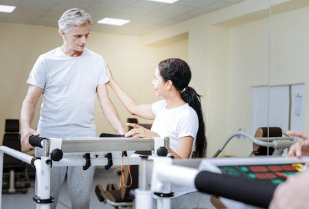 Calm aged man feeling ready for doing the exercises while being in a modern convenient gym and looking attentively at his kind professional qualified trainer Фото со стока