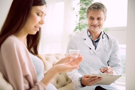 Professional therapist. Delighted nice skillful doctor smiling and observing his pregnant patient while taking notes