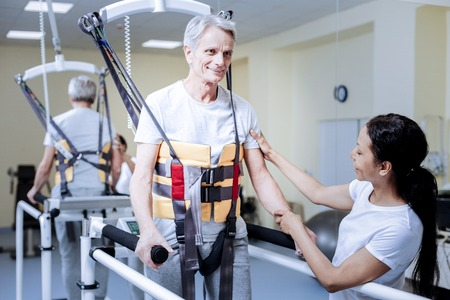 Rather convenient. Calm cheerful senior patient spending the day in a rehabilitation center with a kind qualified medical worker and learning to walk in a special important body vest