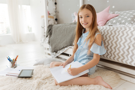 Pretty child keeping smile on her face and sitting near her bed while making notes