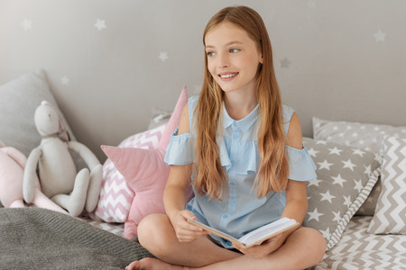Dreamy mood. Positive girl keeping smile on her face and holding book in both hands while looking aside Stock Photo