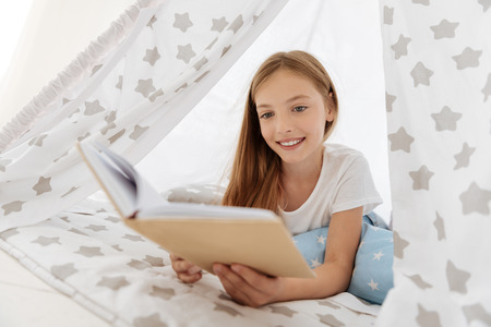 Charming girl leaning on elbows and expressing positivity while lying on pillows