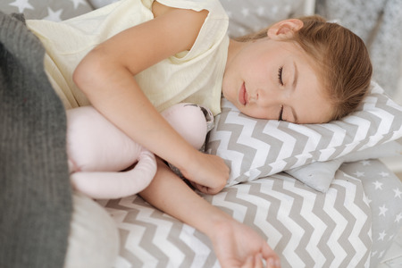 Moment of happiness. Delighted child putting head on the pillow and embracing her toy while resting at daytime