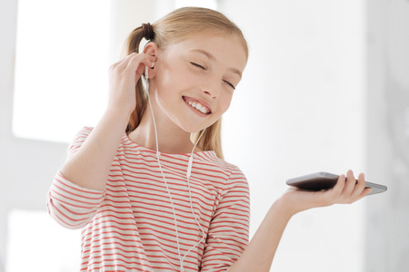 Music lover. Attractive girl keeping eyes closed and wearing earphones while being very pleased