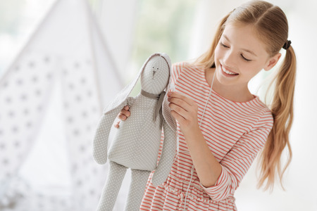 Handmade toy. Cheerful girl expressing positivity and bowing head while spending time with pleasure Stock Photo