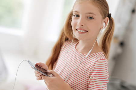 Happy to be here. Attractive kid expressing positivity while holding telephone and looking straight at camera Stock Photo