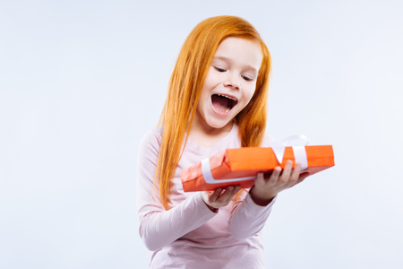 My gift. Joyful red haired girl feeling very excited while receiving a gift