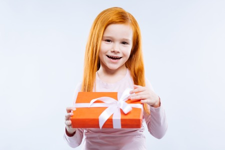 So curious. Cheerful positive girl wanting to open the present while being curious about it