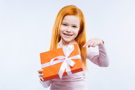 Great surprise. Delighted cute girl smiling while pointing at the present Stock Photo
