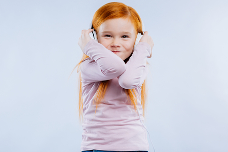 Best relax. Joyful red haired girl smiling while enjoying listening to music