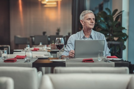 Creating plan. Handsome senior man sitting in front of laptop while working with pleasure