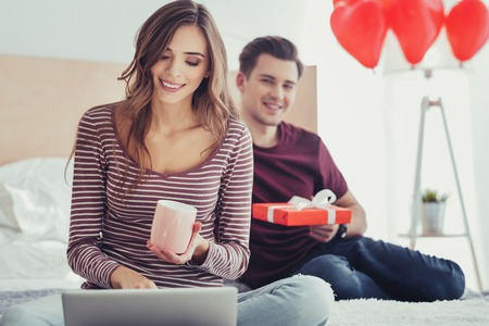 Nice choice. Portrait of adorable delighted girl holding a cup in hand and using a laptop while her boyfriend sitting on bed with a present and observing his girlfriends behavior