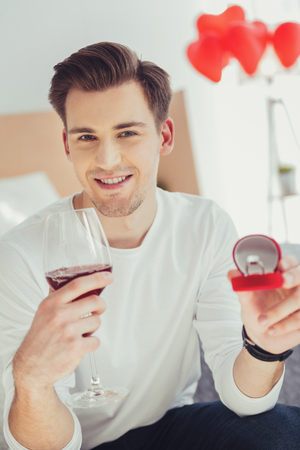 Planning proposal. Portrait of young pleased man looking at you with a smile while holding a glass of wine and wedding ring Stock Photo