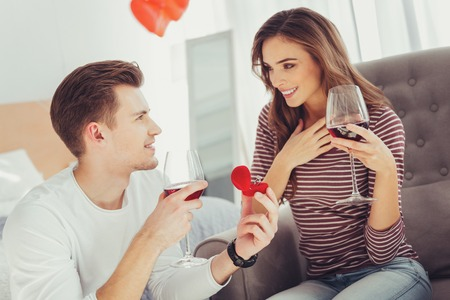 So unpredictable. Portrait of young beautiful girl being pleased while her delighted boyfriend presenting a wedding ring and making a proposal Stock Photo