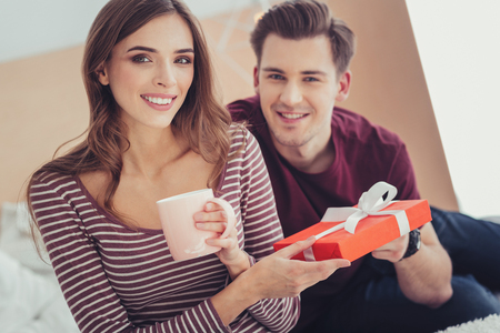 Lovely date. Portrait of young charming couple looking at you with amusement while holding a splendid present and expressing happiness
