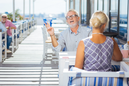 Bring two. Pleasant aged man gesticulating while ordering two glasses of wine in the restaurant