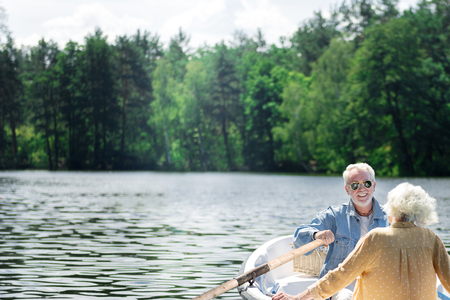Handsome pensioner. Cheerful emotional elderly man smiling to his wife while rowing the boat