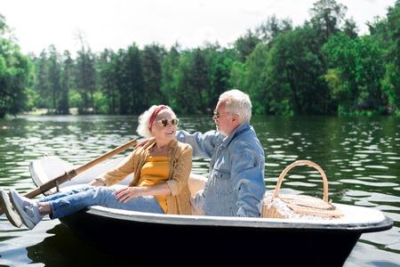 Praat in de boot. Rustige positieve senior vrouw die zich tot de echtgenoot wendt terwijl ze in de boot naast hem zit