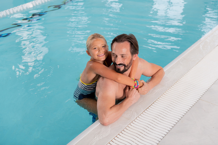 Happy fatherhood. Joyful nice girl swimming with her father while being with him in the pool Stock Photo