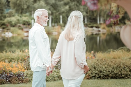 Walk with him. Joyful bearded man keeping smile on his face while holding hand of his wife