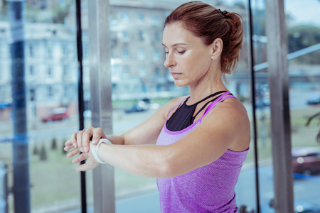Monitor your health. Focused mature woman using fitness tracker and posing near window