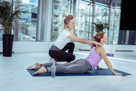 Body awareness. Happy mature woman doing yoga asana while trainer speaking with her