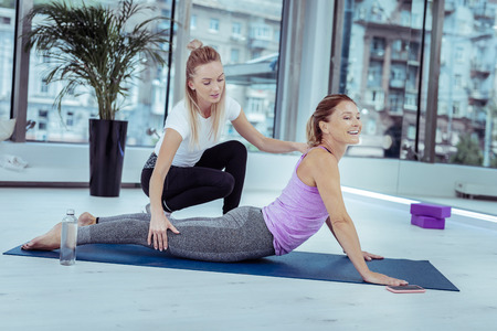 Yoga for you. Cheerful mature woman doing yoga asana while trainer talking to her